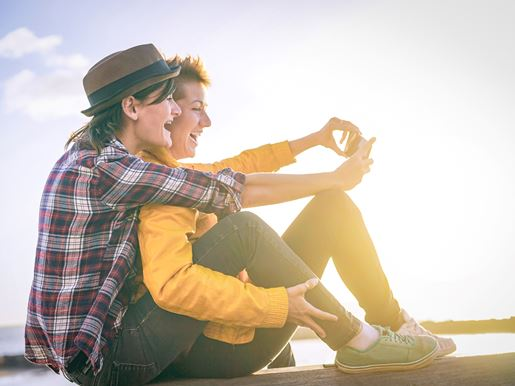Canva Happy Lesbian Couple Taking A Selfie With Mobile Smart Phone Camera On The Beach At Sunset Vignette Edit Homosexuality, Diversity, Vacation, Travel, Lgbt, Technology Concept